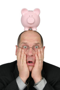 Business man with Piggy Bank on top of his head and hands on face